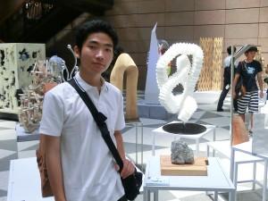 自らの作品展示の前で「作品=石の模刻(木の台の上)」