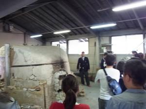 陶芸デザインコースの窯の前で所属生徒が説明。